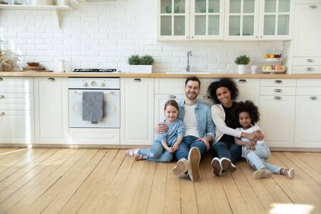 Foto de Portrait of happy multiracial young family with little kids sit on warm floor in design modern kitchen, smiling multiethnic parents with small biracial daughters relax in new renovated home together - Imagen libre de derechos