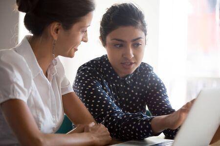Photo pour Diverse businesswomen discuss analyse online project look at laptop screen colleagues brainstorming strategizing together, mentor helping apprentice explain corporate program, support teamwork concept - image libre de droit