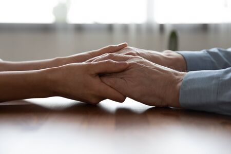 Photo for Young woman doctor, adult daughter, carer or medical nurse holding older man hands of senior father, elder patient on table. Retired people health care, medicare and homecare concept. Close up view - Royalty Free Image