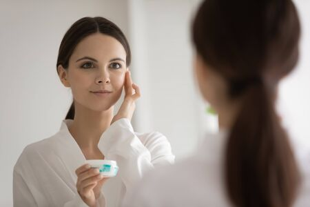 Foto de Beautiful young Caucasian woman look in mirror apply use moisturizing face cream for healthy glowing skin, millennial female do daily facial procedures at home, put beauty product, skincare concept - Imagen libre de derechos