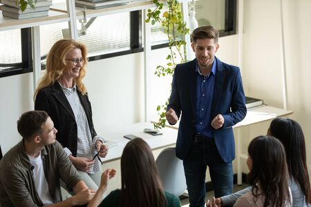 Confident male leader, coach holding briefing for young and mature team employees in office, explaining business strategy, plan to subordinates. Businessman at company meeting with diverse colleagues.