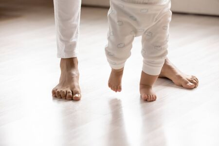 Photo for Crop close up of small biracial toddler infant make first steps on home wooden floor holding mom hands, little african American baby child learn walking with mother support care, childcare concept - Royalty Free Image
