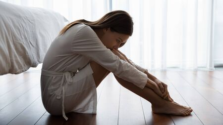 Photo pour Sad young woman in white nightrobe sit barefoot on floor in bedroom leaned head to knees looking unhappy, suffers from loneliness, break up divorce with husband, hard decision about abortion concept - image libre de droit
