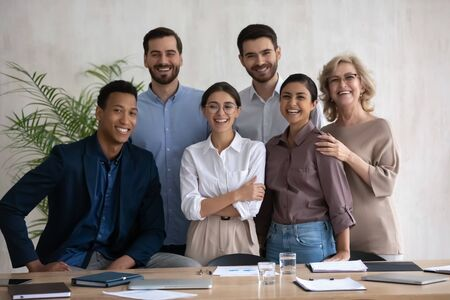 Photo pour Portrait picture of smiling diverse employees stay together laughing looking at camera. Happy businesswoman with african american and caucasian businessmen, mature and indian ethnic female colleagues. - image libre de droit
