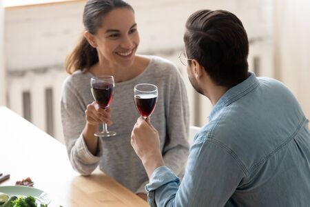 Smiling young husband and wife sit in modern kitchen drink red wine enjoy family leisure domestic weekend together, happy millennial couple celebrate wedding anniversary or romantic date at home