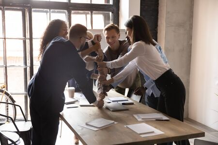 Photo pour Excited business people stacking fists at table, engaged in team building activity at corporate meeting in boardroom, smiling colleagues celebrating success, teamwork result, business achievement - image libre de droit
