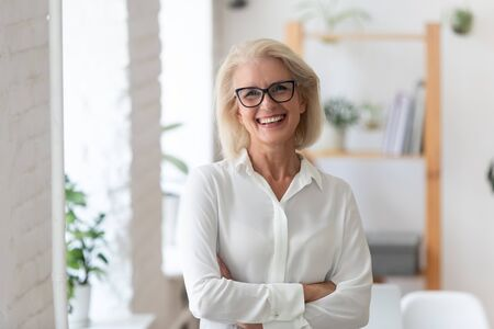 Photo pour Portrait of smiling senior businesswoman in glasses standing posing in modern office, happy confident middle-aged female employee or CEO look at camera show confidence and success at workplace - image libre de droit
