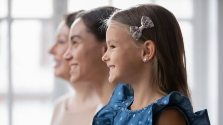 Foto de Close up profile view of smiling three generations of women look in distance bright future dreaming or visualizing together, happy girl with young mom and mature grandmother show unity, bonding - Imagen libre de derechos