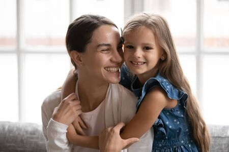 Photo pour Portrait of smiling little preschooler girl child hug happy young mom show gratitude and love, cute small daughter and Caucasian mother embrace cuddle, enjoy tender family moment relaxing at home - image libre de droit
