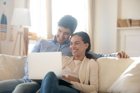 Photo pour Happy young caucasian couple sit relax on couch in living room use laptop enjoy family weekend together, smiling millennial man and woman rest on sofa at home, watch video online on computer - image libre de droit