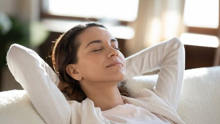 Photo pour Close up of calm millennial Caucasian girl lying relaxing on couch at home sleep or take nap, relaxed young woman rest on sofa, breathe fresh air, relieve negative emotions, stress free concept - image libre de droit