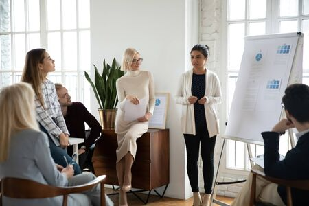 Photo pour Young focused indian female speaker coach standing near whiteboard, giving marketing research results presentation or training to focused diverse colleagues employees businesspeople in modern office. - image libre de droit