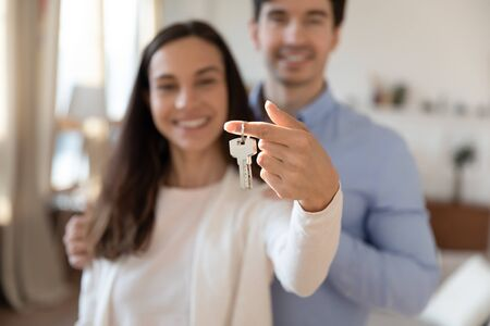 Close up focus of excited caucasian couple hold show keys moving together relocating to own house, happy man and woman buy first shared apartment dwelling together, new home, realty concept