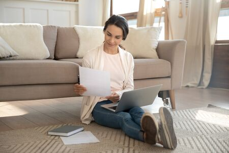 Young Caucasian woman sit on warm floor in living room working on laptop with paperwork documents, millennial girl relax at home, studying on modern computer gadget, online education concept