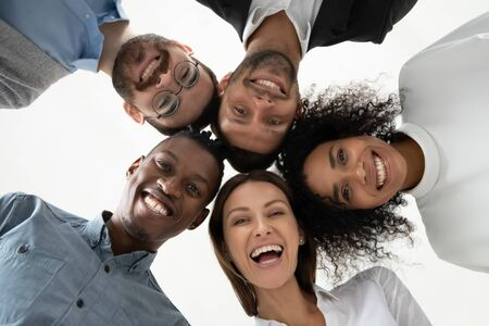 Photo pour Portrait close up bottom view happy faces of diverse employees team standing in circle, looking at camera, smiling businesswomen and businessmen engaged in team building, posing for photo - image libre de droit