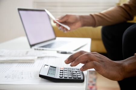 Photo pour Manage planning family budget, savings and payment concept. Close up image hands of African man using calculator calculates finances checking family expenses, do small business, month result analysis - image libre de droit