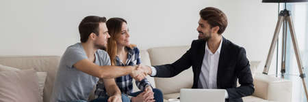Photo pour Happy couple young family flat renters shake hands with realtor seated on sofa in living room. Make real estate deal, first dwelling purchase concept. Horizontal photo banner for website header design - image libre de droit