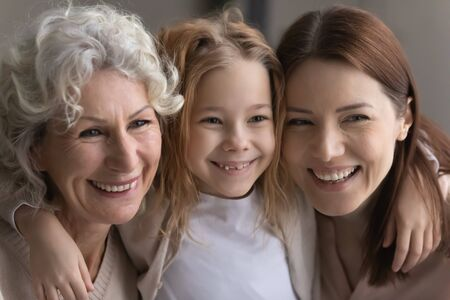 Photo pour Close up portrait of happy three generations of women hug and cuddle show family unity and support, caring little girl with young mother and mature grandmother embrace, show love and bonding - image libre de droit