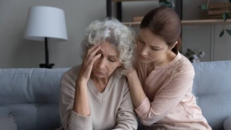 Foto de Supportive grownup girl hug comfort caress upset lonely elderly 60s mother mourning at home, caring adult daughter embrace show love and support to sad distressed senior mom, family unity concept - Imagen libre de derechos