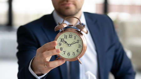 Foto de Crop close up of businessman hold show clock notify about deadline or time frame for new company project launch, male employer specify task startup limit, note about business meeting appointment - Imagen libre de derechos