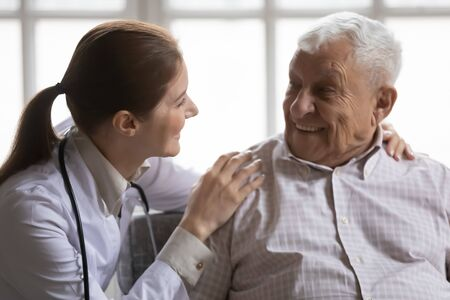 Photo pour Close up caring female doctor wearing uniform with stethoscope talking to smiling older man, young woman caregiver supporting elderly patient, touching shoulders, warm relationship, healthcare - image libre de droit