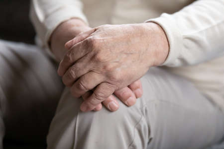 Close up elderly lonely man folded wrinkled hands on lap, mature old grandfather sitting alone, thinking about past, lost in thoughts, aging process concept, loneliness and solitude