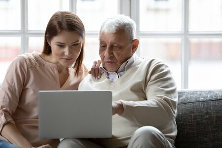 Foto de Young woman and older man using laptop together, looking at screen, sitting on couch at home, mature father asking questions to grownup daughter, studying to use computer, pointing at screen - Imagen libre de derechos