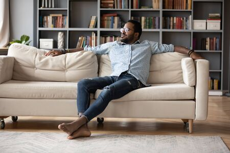 Photo pour Carefree relaxed african man resting sit on sofa in cozy living room looking out the window enjoy lazy free day. Warm home owner, modern rented apartments, breath fresh conditioned air indoor concept - image libre de droit