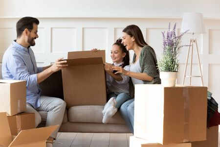 Photo for Adorable daughter helping parents with cardboard boxes on moving day, happy family with child sitting on couch, unpacking belongings in modern living room, relocation and mortgage concept - Royalty Free Image