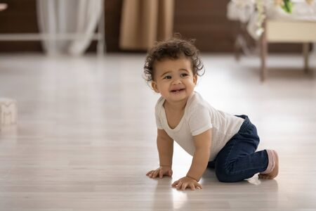 Photo pour Cute barefoot toddler African American girl crawling on warm wooden floor with underfloor heating at home, pretty adorable baby little child learning to walk, first steps on hands and knees - image libre de droit