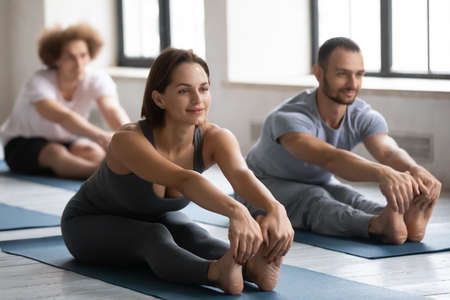 Foto für Happy young beautiful european appearance woman touching barefoot toes, stretching back and legs muscles in seated forward bend pose, practicing yoga with friends at group exercise indoors in club. - Lizenzfreies Bild