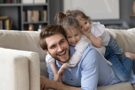 Photo pour Two cute little girls lying on smiling father back, relaxing on cozy couch together, enjoying leisure time, lazy weekend, happy young dad and affectionate preschool daughters having fun at home - image libre de droit