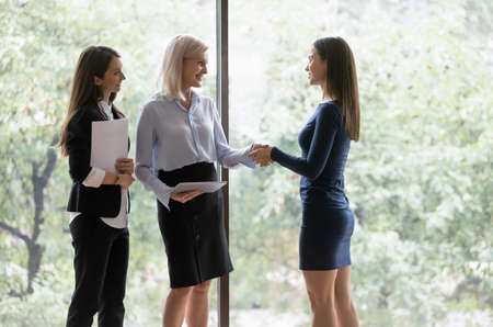 Photo pour Middle-aged businesswoman greeting millennial female colleague different age business women shake hands express respect smiling, good first impression, hr manager congratulate hired applicant concept - image libre de droit