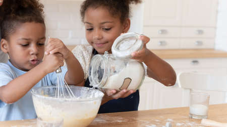 Photo pour Cute little african american brother and sister kids have fun preparing dough for cookies or pie in kitchen, happy small biracial children siblings make surprise for parents, baking cooking at home - image libre de droit