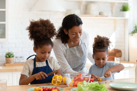 Photo pour Loving young african American mother or nanny teach little kids prepare healthy food or salad at home kitchen, caring happy biracial mom cooking together with small ethnic children son and daughter - image libre de droit