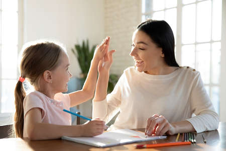 Photo pour Happy young mother and little daughter giving high five close up, having fun, drawing colorful pencils, sitting at desk together, smiling mum and preschool girl enjoying leisure time at home - image libre de droit