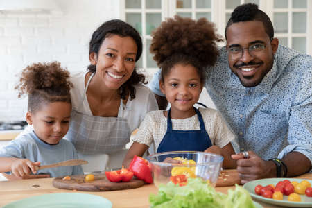 Photo pour Portrait of smiling young african American family with little kids cooking together in kitchen at home, happy loving biracial parents teach small children prepare food make healthy salad dinner - image libre de droit
