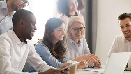 Foto de Smiling diverse employees listening to businesswoman coach at briefing, mentor explaining strategy, training staff, using laptop, helping with software, team building activity, horizontal photo - Imagen libre de derechos