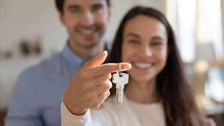 Photo pour Close up young excited couple showing keys in hands to camera. Happy homeowners celebrating moving in new apartment or last banking mortgage payment, feeling glad of purchasing property, real estate. - image libre de droit