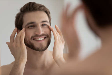 Photo pour Close up mirror reflection smiling satisfied young man touching skin under eyes, applying anti aging moisturizing cream or lotion, standing in bathroom, enjoying skincare procedure, morning routine - image libre de droit
