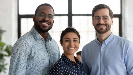 Head shot portrait smiling successful diverse employees team standing in modern office, happy overjoyed Indian businesswoman, African American and Caucasian businessmen looking at camera