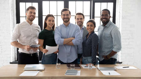 Corporate photo smiling diverse employees with confident executive wearing glasses standing in modern office room, looking at camera, successful startup founder with team, staff members