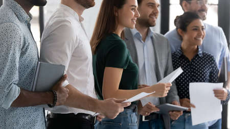 Close up successful diverse employees holding paper sheets standing in modern office room, motivated happy workers business team members, company staff, department, unity and teamwork concept