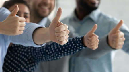Close up diverse employees showing thumbs up together, team building, happy overjoyed colleagues recommending best corporate service, good career opportunities, human resources and employment concept