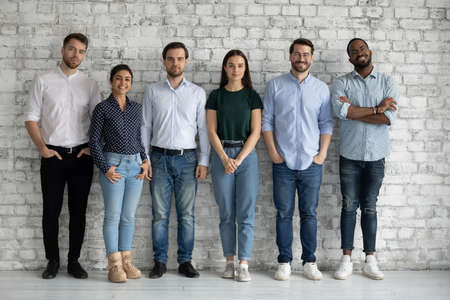 Full length portrait motivated successful diverse employees team standing in modern office near bricks wall together, confident smiling business people colleagues staff posing for corporate photo