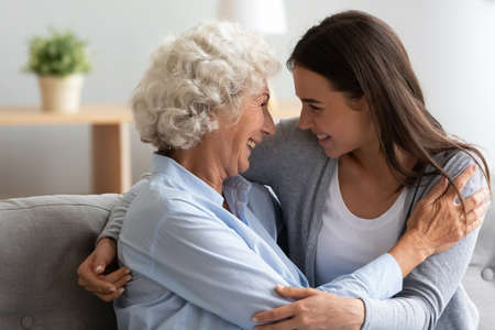 Photo pour Overjoyed senior older hoary woman cuddling smiling pretty millennial grownup daughter, enjoying trustful conversation at home, laughing joking having fun while spending weekend time together. - image libre de droit
