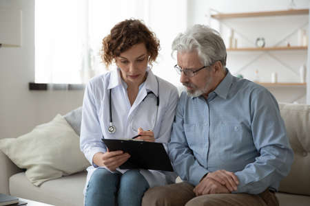 Photo for Young woman doctor nurse consulting mature patient during homecare visit, holding clipboard, filling card, illness history, therapist gp giving recommendations to senior man, sitting on couch at home - Royalty Free Image