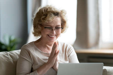 Foto de Smiling overjoyed mature woman wearing glasses reading good news, using computer, looking at laptop screen, watching video in social network, shopping online, received great shopping offer - Imagen libre de derechos