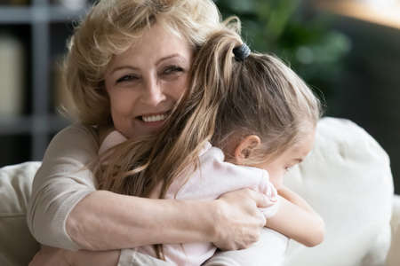Photo pour Close up smiling loving mature woman grandma hugging little granddaughter, happy grandmother and pretty girl enjoying tender moment, cuddling, spending leisure time together at home - image libre de droit