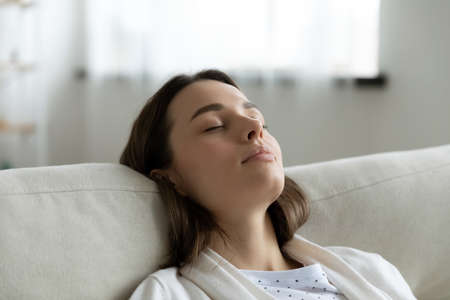 Photo pour Close up head shot tired millennial woman leaning on cozy couch, enjoying lazy stress free weekend time at home. Tranquil peaceful young girl napping with closed eyes on sofa, daydreaming indoors. - image libre de droit